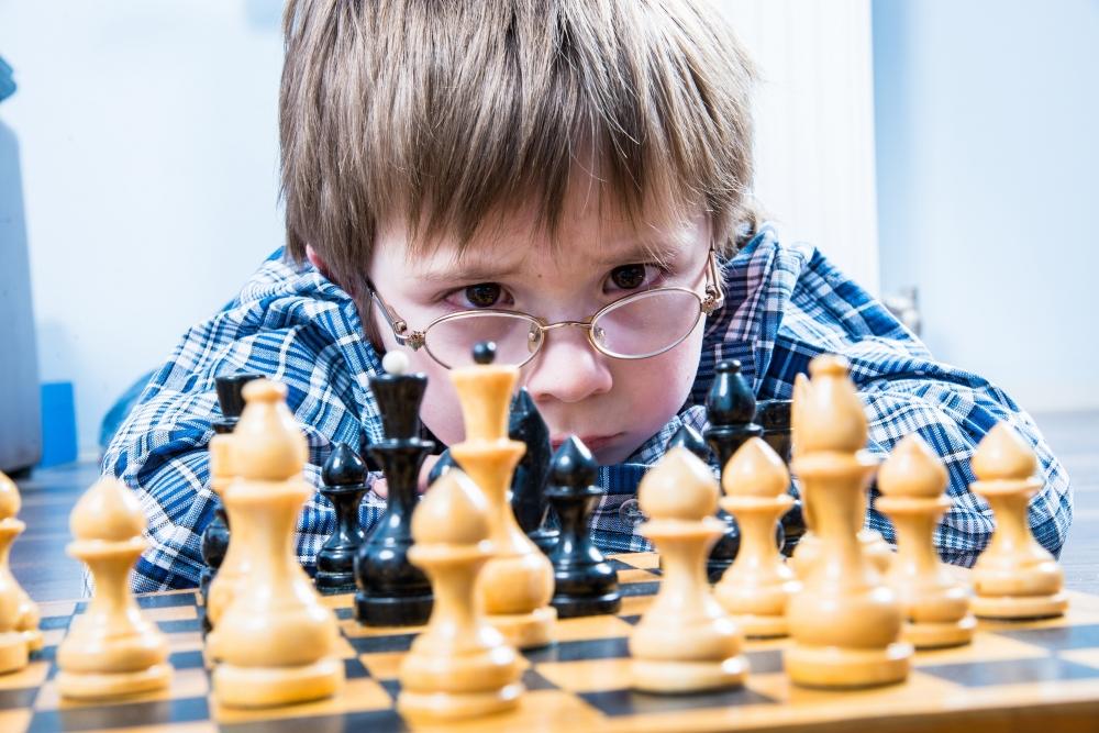 Chłopiec rozmyśla nad partią szachów