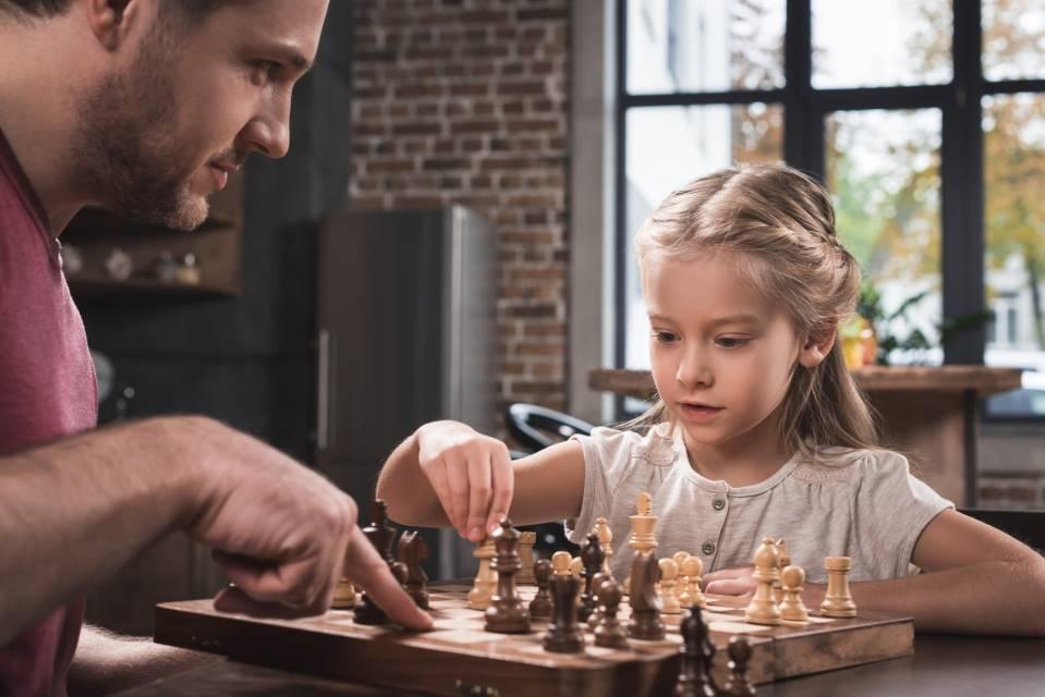 dziewczynka gra w szachy z ojcem