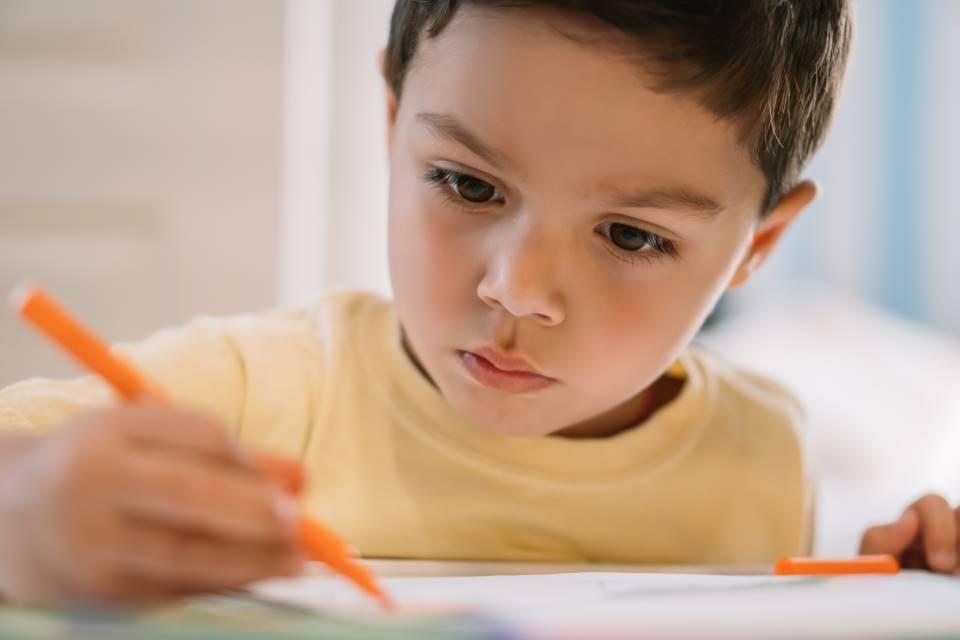chłopiec skupia się na grze i pisaniu